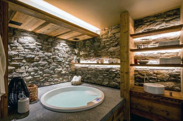 Rustic master bathroom with a chandelier, stone accent walls and tile  flooring